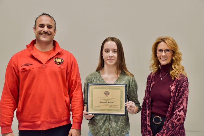 Norman North High School senior Savannah Mitchell, center, was awarded this year's Norman Crime Stoppers' John Dutch Memorial Scholarship. Pictured with Mitchell are Mario Palumbo, left, president of the International Association of Fire Fighters Local 2067,  and Tonja McCawley, Crime Stoppers Board president.
