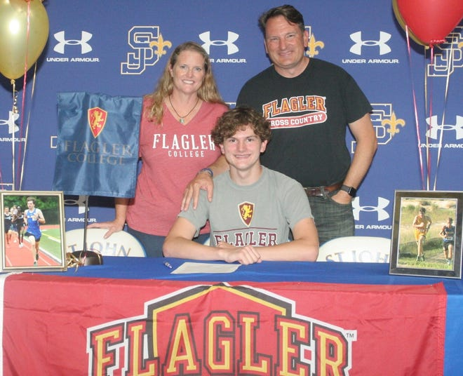 St. John Lutheran senior Tristan Fratello, center, signed a scholarship to run cross country at Flagler College as mother, Rebecca Fratello, and father, Jay Fratello, look on during Wednesday's ceremony.