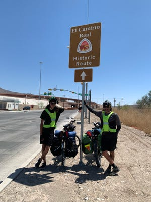 Ryan Ortega, right, and Ty Ortega, both of Pekin, take a break from their cross-country bicycle ride under an El Camino Real marker near El Paso, Texas.