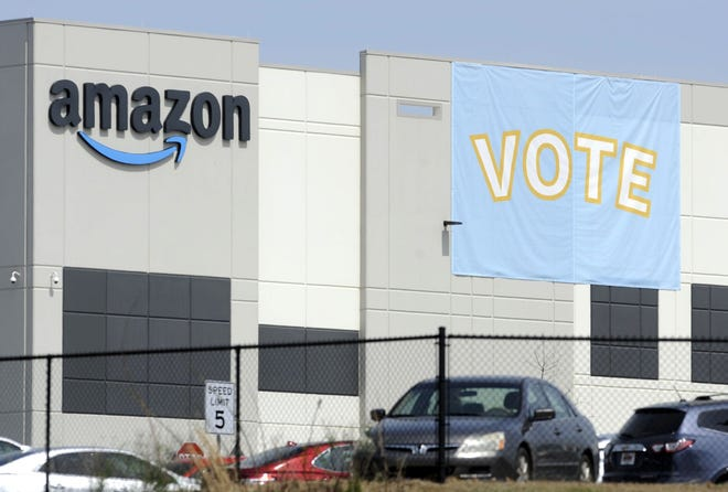A banner encouraging workers to vote in labor balloting is shown at an Amazon warehouse in Bessemer, Ala., on March 30. The retail union that failed to unionize Amazon workers at the Alabama warehouse wants the results to be thrown out, saying that the company illegally interfered with the voting process. The Retail, Wholesale and Department Store Union said in a filing that Amazon threatened workers with layoffs and even the closing of the warehouse if they unionized.