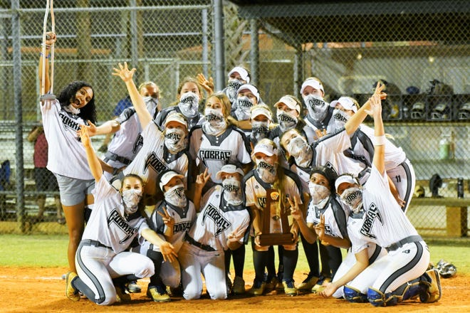 The Park Vista softball team celebrates with a funny pose and the district trophy after winning the district final against Spanish River, defeating the visitors 10-2 on Wednesday night.