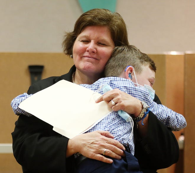 Sen. Maryellen Goodwin, who is battling colon cancer, gets a hug from her nephew Liam Connelly, 9, as Gov. Dan McKee signs legislation named in her honor.