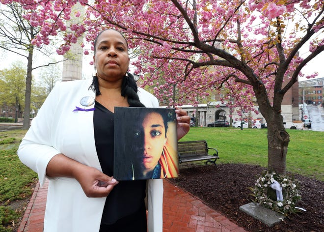 Gem Barros holds a painting of her daughter Shemeeka, who was a victim of gun violence in 2012.
