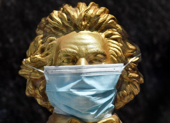 A golden bust shows Germany's most famous composer, Ludwig van Beethoven, with a face mask in a shopping window in Bonn, Germany.