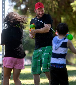 Charles Dougherty IV, center, is doused by his 11-year-old daughter Chyann Dougherty, left, and 6-year-old nephew Mason Guyer during a squirt-gun fight at Louis Park in Stockton on April 28.