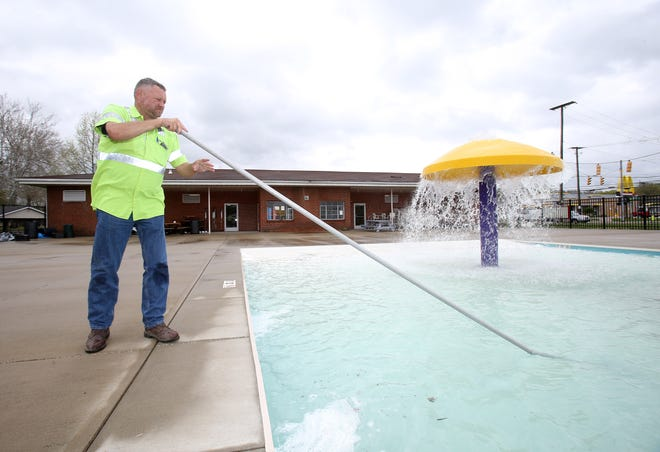 JT Williams, service director for Minerva, scrubs the bottom of the Minerva Public Pool in preparation for its upcoming Memorial Day weekend opening.