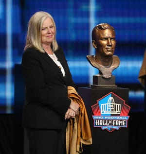 Sue Withers smiles besides the bust of her father Ed Sprinkle as one of the newest members of the Pro Football Hall of Fame at Umstattd Hall in Canton on Wednesday, April 28, 2021. The event posthumously recognized his contributions to the game.