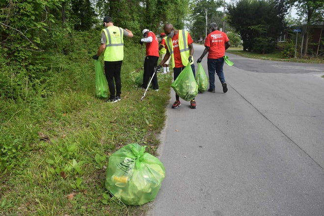 Volunteers work along Garden Street in Duffyfield during Thursday's opening of a three-day Community Cleanup conducted by a coalition of New Bern non-profits.