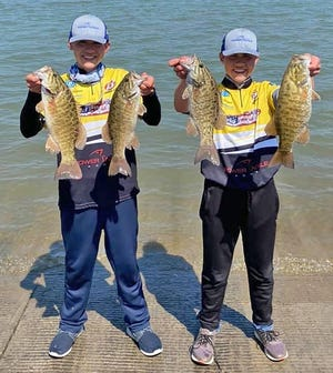 Topeka twins Nick and Kyle Herrman hold up their winning bass after taking first place April 25 at the 2021 Kansas SAF/TBF Junior State Championship on Melvern Reservoir.