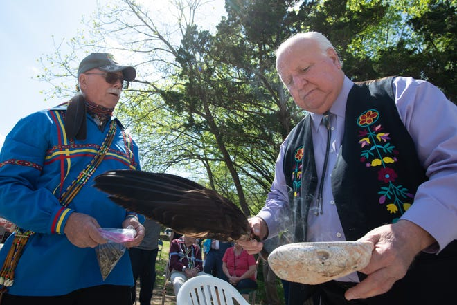 """Citizens Potawatomi Nation Chairman John """"Rocky"""" Barrett, right, waves an eagle's wing across a mix of burning sage, sweet grass, tobacco and cedar, known as """"the four sacred medicines"""" in some cultures, for those wanting a blessing following a dedication Thursday at Burnett's Mound."""