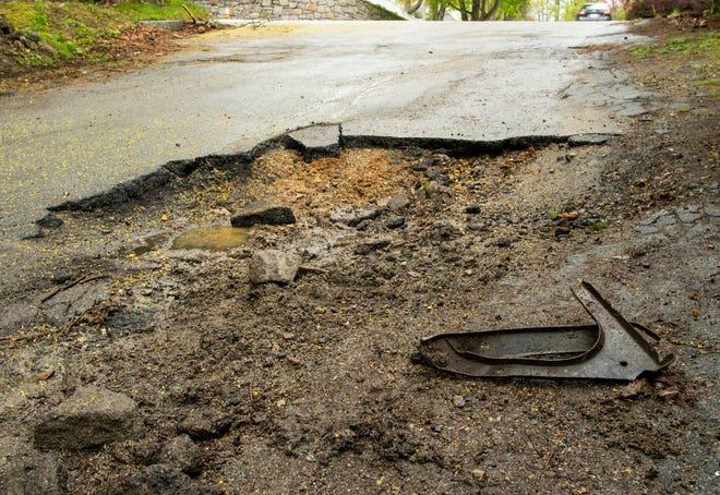 A piece of metal that appears to be from the underside of a vehicle sits in a large pothole on Annisquam Street in Worcester Thursday.