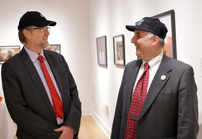 Wearing baseball hats from each other's respective institutions, Fitchburg Art Museum director Nick Capasso, left, and Fitchburg State University President Richard Lapidus share a laugh Thursday after signing an alliance on future endeavors.