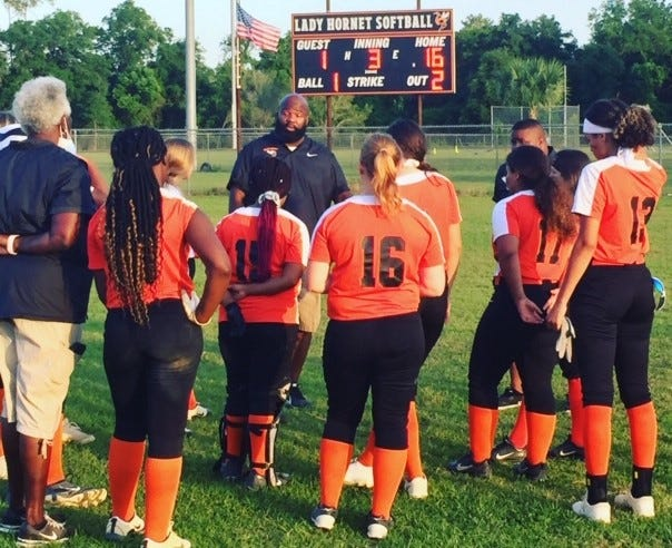 Hawthorne softball coach CJ Hawkins talks to his Hornets following their 16-1 win over Crescent City on Wednesday.