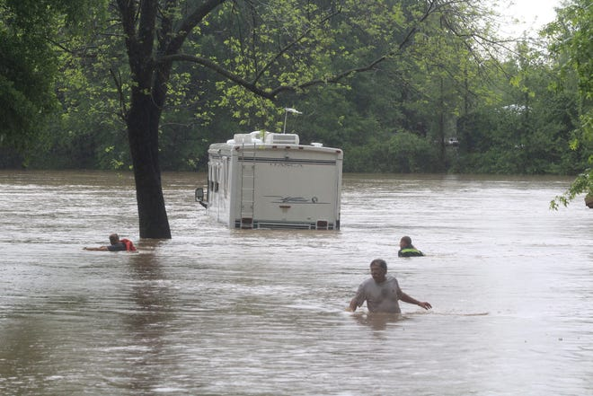 A man who declined to give his name helps a tow truck operator take a cable to his partially submerged mobile home during floods at Clear Creek Park Thursday, April 29, 2021, in the Alma area.