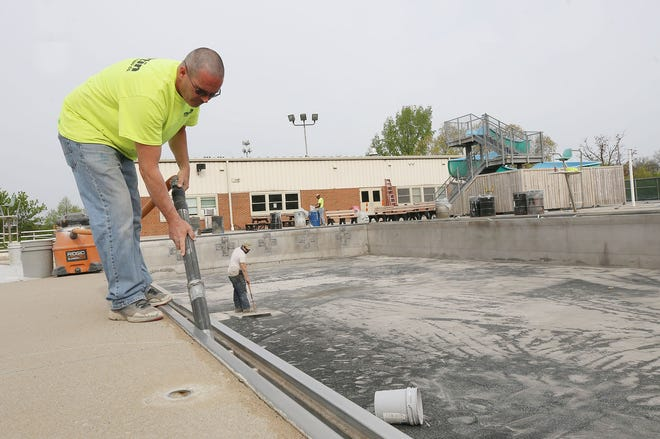 Shaun Wells with Martin Painting and Coating cleans out the drain system at Worthington Pools on April 28. Crews were sandblasting the pool and deck and later will power wash and paint. The pool will reopen over Memorial Day weekend.