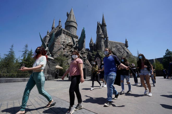 Young people wear mandatory face masks at the Wizarding World of Harry Potter at Universal Studios Hollywood theme park as it officially reopens to the public at 25% capacity with COVID-19 protocols in place in Los Angeles, Friday, April 16, 2021.