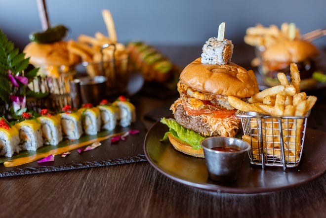 The Madness Burger is topped with spicy crab salad and a sushi roll.