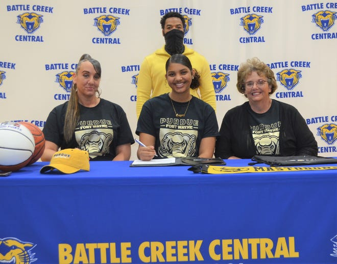 Battle Creek Central standout Arieonna Ware signs her National Letter of Intent to play college basketball at Division I Purdue Fort Wayne at a ceremony Thursday at the BCC Field House. She is joined by her family Sue Heinen and Stephanie Heinen and BCC coach Tony Warren.