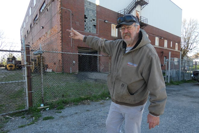 Tom Manely, the new owner of the former Swan Rubber building on East Mansfield Street, indicates where he plans to add parking.