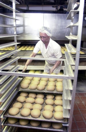 David On of Burlington bakes whole wheat rolls at the Koffee Kup Bakery in Burlington in 2003. Koffee Kup Bakery closed this week after more than 80 years in business.