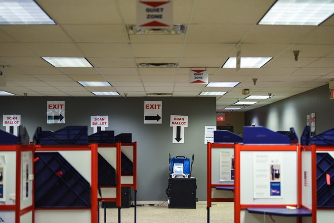 Signs line the walls and floor to guide early voters along and keep them safe at the Hamilton County Board of Elections.