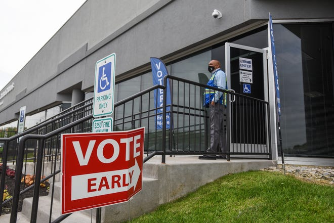 Tyrone Patrick holds open doors for voters as early voting takes place at the Hamilton County Board of Elections.