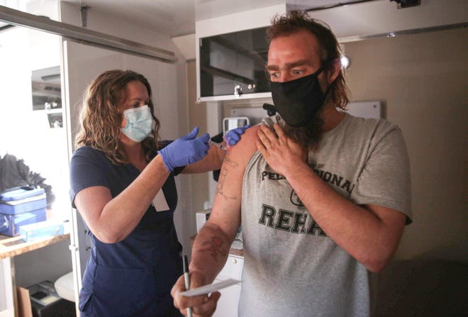 Teresa Copple, a registered nurse with Primary Health Care, Inc., administers a shot of Johnson & Johnson COVID-19 vaccine to Daniel Neal, a Des Moines homeless resident, during a mobile vaccine clinic on Thursday, April 29, 2021, in Des Moines.