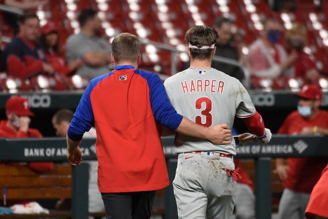 Philadelphia Phillies right fielder Bryce Harper, right, is helped off the field after getting hit by a pitch during the sixth inning of the team's baseball game against the St. Louis Cardinals on Wednesday, April 28, 2021, in St. Louis.