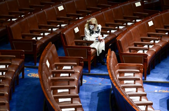Rep. Debbie Dingell, D- Mich., looks at paper put on seats for social distancing as she waits in her seat ahead of President Joe Biden speaking to a joint session of Congress, Wednesday, April 28, 2021, in the House Chamber at the U.S. Capitol in Washington.