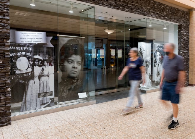 Shoppers walk past an exhibit showcasing photographs of African American women and the suffrage movement installed by the Evansville African American Museum and the Evansville Museum of Arts, History & Science in an empty storefront at Eastland Mall Thursday afternoon, April 29, 2021.