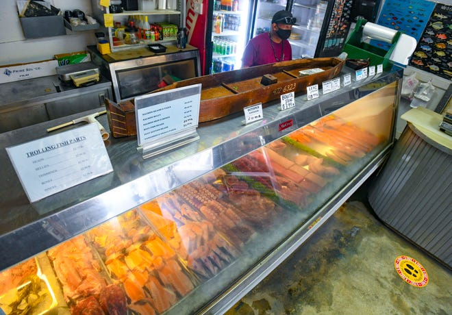 Fresh tuna and salmon filets, cut octopus pieces and other seafood products are displayed in a refrigerated showcase ready for purchase at the Fishermen's Co-Op store in Hagåtña on Thursday, April 29, 2021.