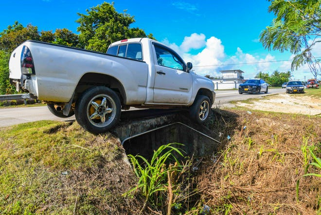 Guam Police Department officers conduct an investigation of an auto ran-off roadway incident, involving a driver who collided a white 2005 Toyota Tacoma pickup into guardrails over a culvert, along Santa Monica Avenue in Dededo on Thursday, April 29, 2021. The male driver, who was the sole occupant in the vehicle, was transported to Guam Regional Medical City, according to Cherika Chargualaf, Guam Fire Department acting spokesperson. CPR was performed on the driver as he was being transported, Chargualaf added. The driver was identified as Abel Sangalang by a family member at the scene.