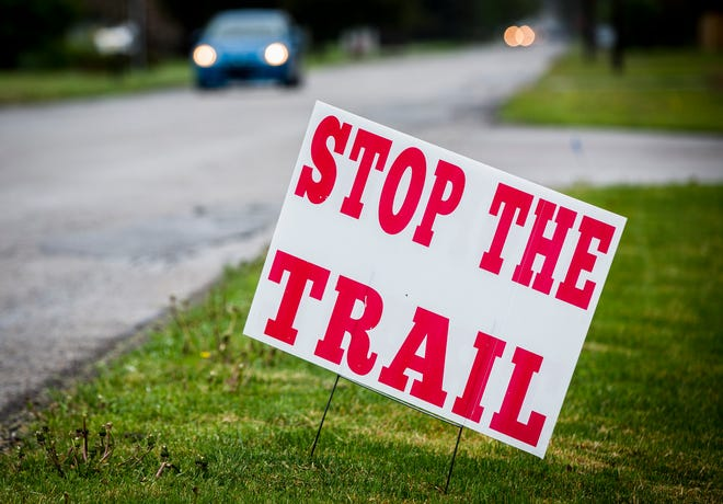 """A """"Stop The Trail"""" sign is positioned near W. Riverside Avenue Wednesday."""