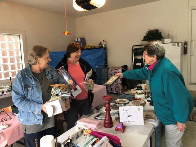 Janet Renwick shows Debbie McGinnis and Mary Ann Neault some of her wares during the South Lyon citywide garage sale, April 29, 2021.