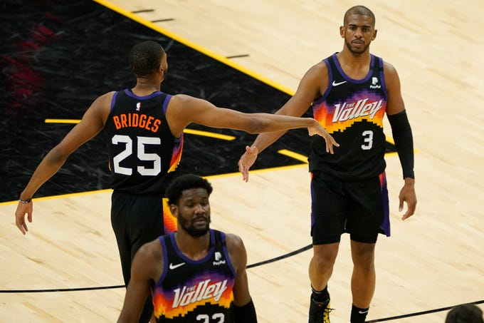 Phoenix Suns guard Chris Paul (3) is greeted by teammate forward Mikal Bridges (25) during the second half of an NBA basketball game against the Los Angeles Clippers, Wednesday, April 28, 2021, in Phoenix. (AP Photo/Matt York).