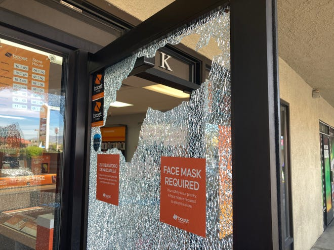 A glass door of a mobile phone business was shattered in a shooting that left two dead in the parking lot of the Mixer Bar April 28, 2021.