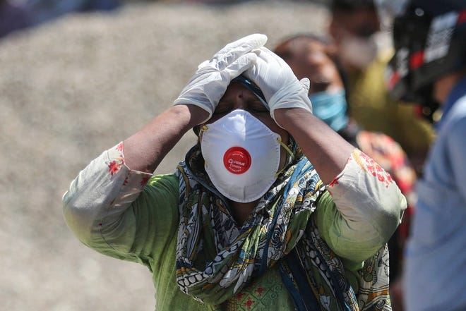 A relative of a person who died of COVID-19 reacts at a crematorium in Jammu, India, April.25, 2021.