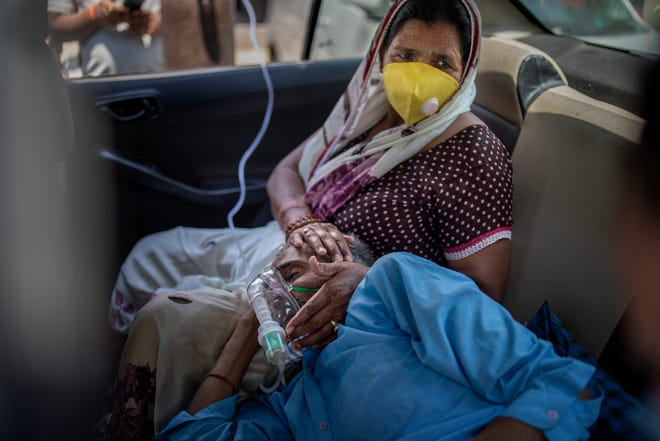 A patient breathes with the help of oxygen provided by a Gurdwara, Sikh place of worship, inside a car in New Delhi, India, Saturday, April 24, 2021. IndiaÕs medical oxygen shortage has become so dire that this gurdwara began offering free breathing sessions with shared tanks to COVID-19 patients waiting for a hospital bed. They arrive in their cars, on foot or in three-wheeled taxis, desperate for a mask and tube attached to the precious oxygen tanks outside the gurdwara in a neighborhood outside New Delhi.