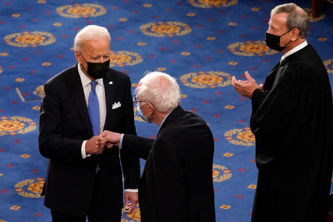 President Joe Biden greets Sen. Bernie Sanders, I-Vt., as Chief Justice of the United States John Roberts watches as Biden arrives to speak to a joint session of Congress Wednesday, April 28, 2021, in the House Chamber at the U.S. Capitol in Washington.