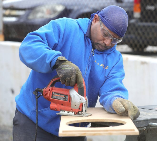 Joseph Easton Sr., owner of LJ Audio Enhancement, cuts a piece of wood for a sound system.