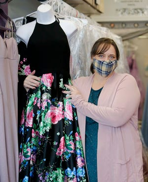 Linda Imrie, the director of Rockin' Frocks, displays one of the dresses on April 30 in Northfield Center.