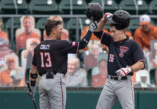 Texas Tech catcher Braxton Fulford (26) and Texas Tech infielder Cal Conley (13) celebrate a score during a Big 12 Conference game Friday at UFCU Disch-Falk Field in Austin.