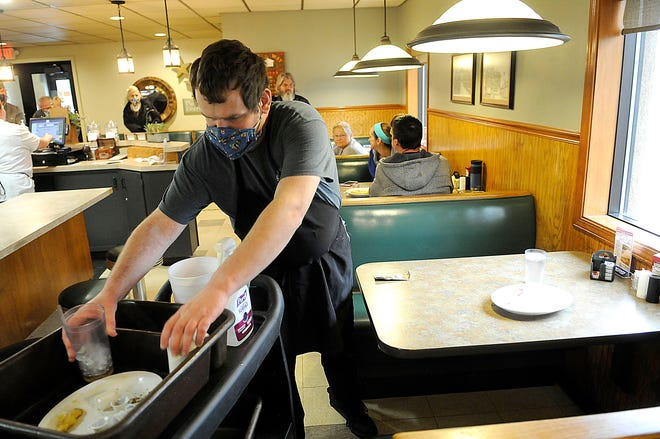 Lynway Restaurant kitchen staff employee David Pervier clears a table on Friday, April 30, 2021. Owner Rob Stoops said they are hiring for all positions. TOM E. PUSKAR/TIMES-GAZETTE.COM
