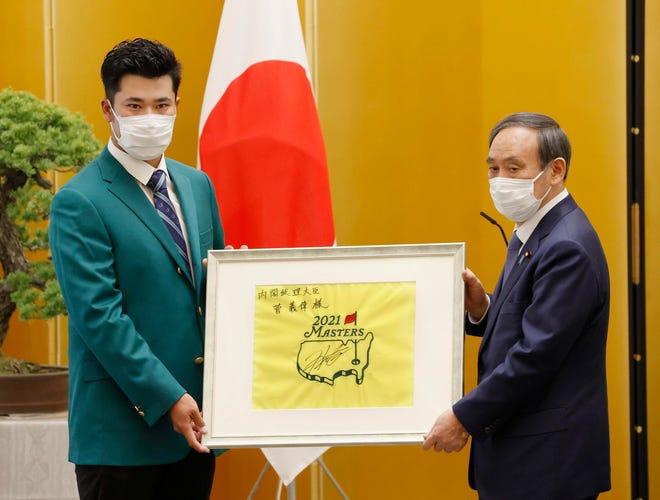 日本のゴルファー松山英樹(左)が2021年4月30日(金)東京国務総理室で菅義偉首相にプレゼントを渡している。 松山は金曜日マスターズゴルフで優勝し、東京で国務総理賞を受けた。 トーナメント。  (APを介してMasanori Takei / Kyodo News)