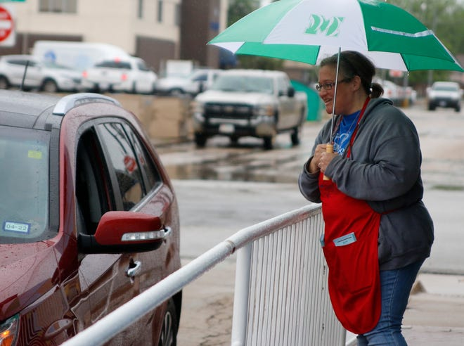 Good Samaritan Ministries board member Linda Lemond stands in a light rain and talks with a motorist early Thursday afternoon during Good Samaritan's Empty Bowls drive-through fundraiser on Clark Street in downtown Brownwood.