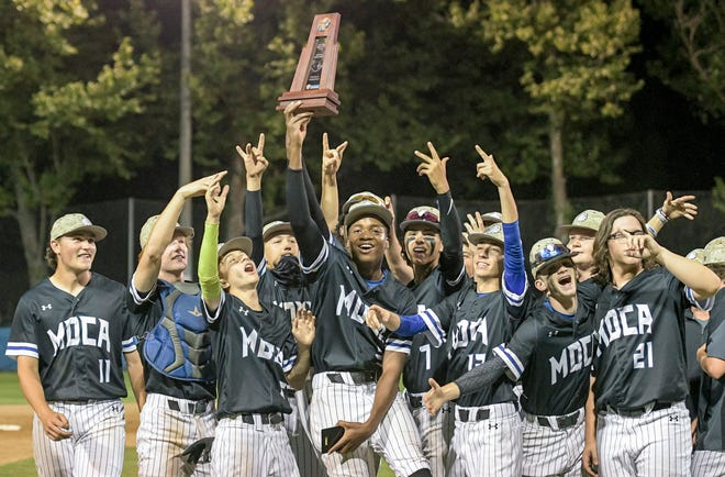 The Mount Dora Christian Academy Bulldogs celebrate after winning the Class 2A-District 5 championship game against Real Life Christian Academy Thursday in Mount Dora. [PAUL RYAN / CORRESPONDENT]