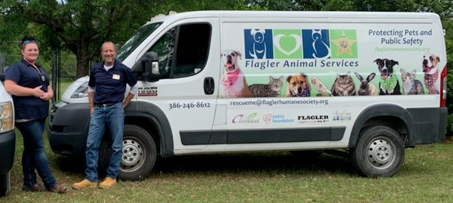 Dawn Morton and Ray Brown stand near one of their Animal Services vans.