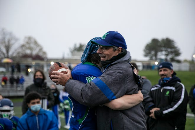 Blue Hills Regional Technical High School varsity football head coach Ed Catabia is hugged by senior Gabriel Polito on Thursday, April 29, 2021 after giving him a game ball.