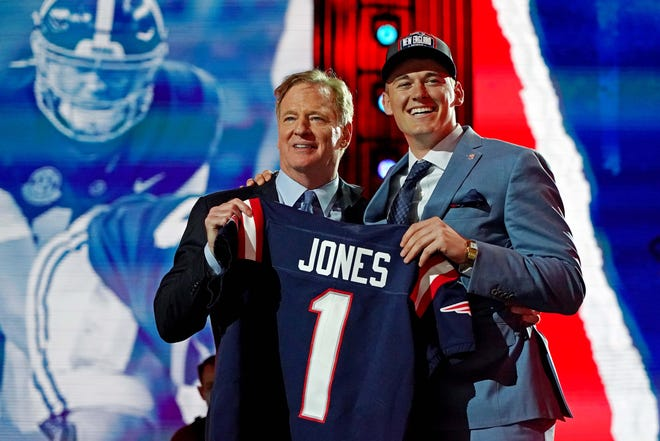 Apr 29, 2021; Cleveland, Ohio, USA; Mac Jones (Alabama) with NFL commissioner Roger Goodell after being selected by the New England Patriots as the number 15 overall pick in the first round of the 2021 NFL Draft at First Energy Stadium.