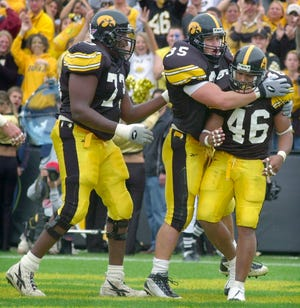 Iowa's Ladell Betts (46) celebrates with teammates Erik Jensen, center, and David Porter, left, after scoring a touchdown against Penn State in a 2001 game. Betts, a former Blue Springs High School star, is returning to Iowa City as the Hawkeyes' running backs coach.